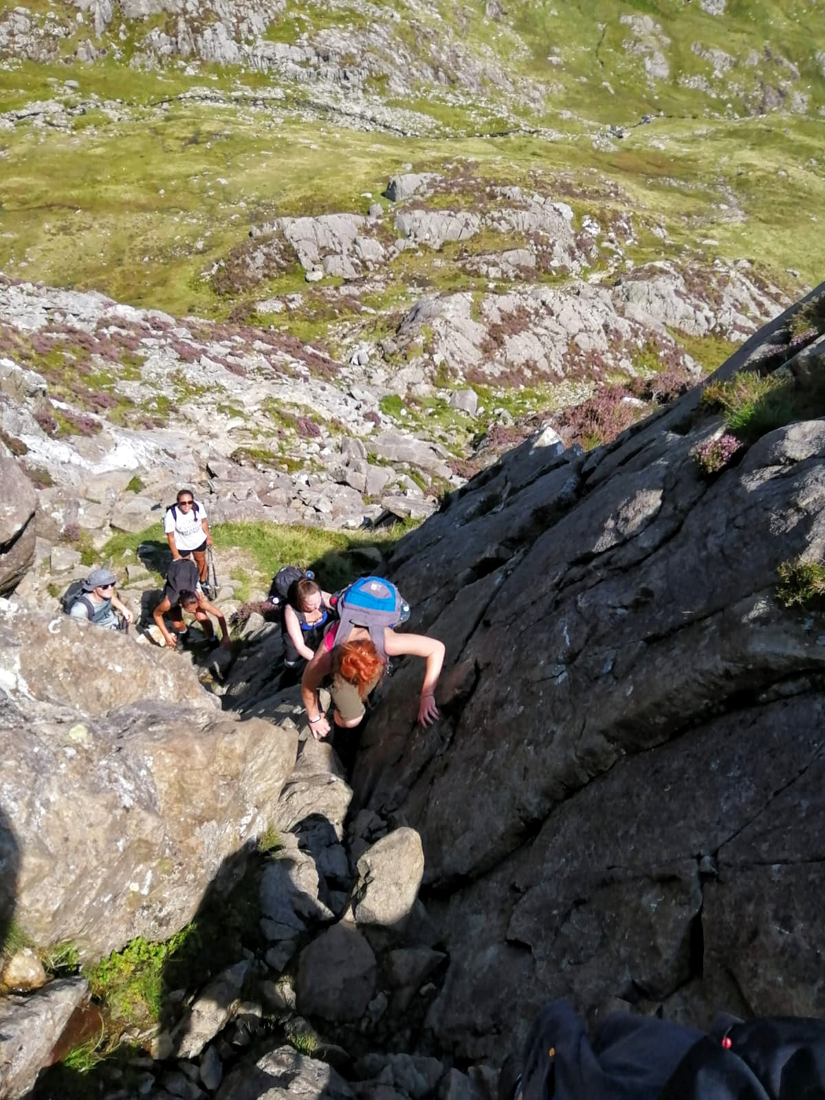A group scrambling to the summit of Pen yr ole wen